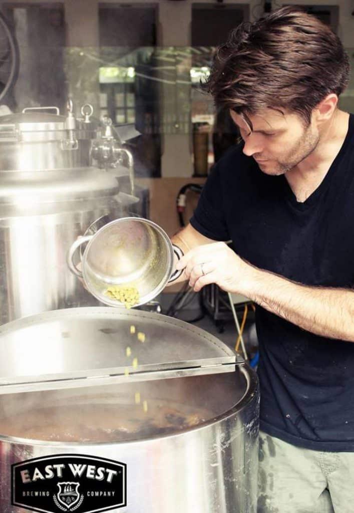 Thợ nấu bia craft vietnam của East West Brewing cẩn thận cho hoa bia vào nồi nấu